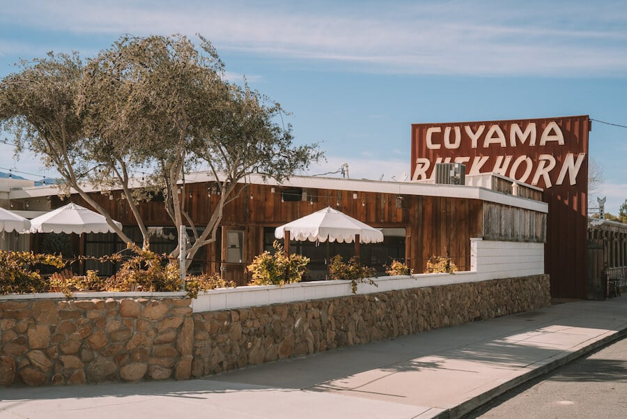 Exterior of Cuyama Buckhorn with retro sign and porch umbrellas