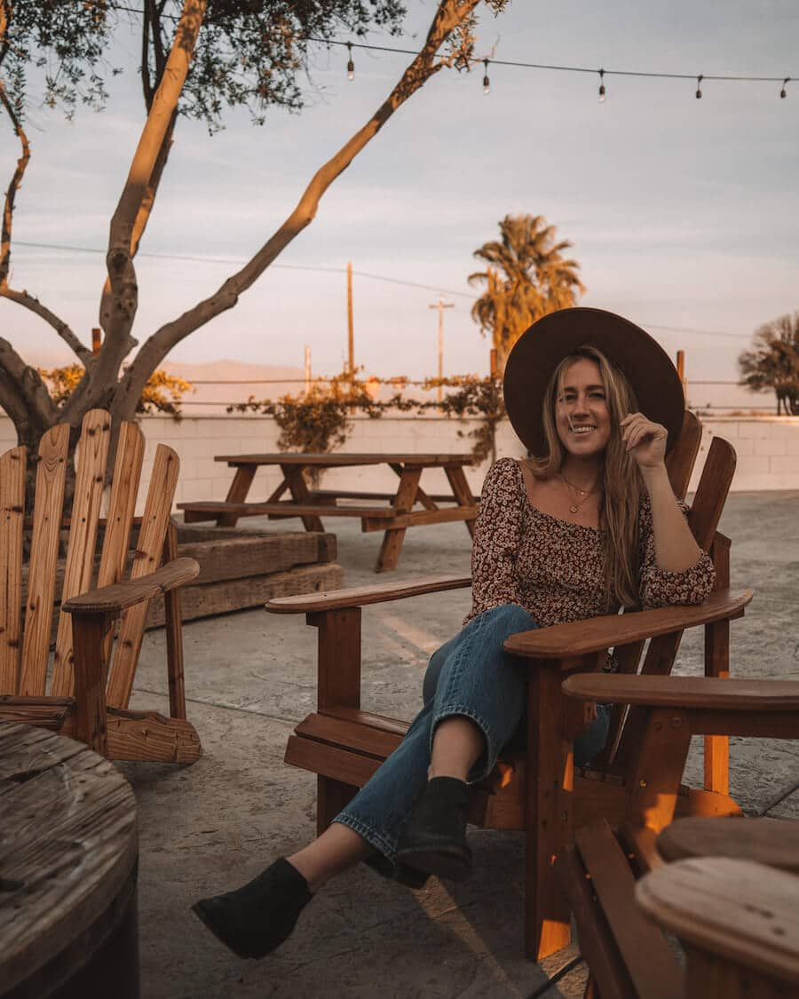 Girl sitting in adirondack chair on the patio of the Cuyama Buckhorn