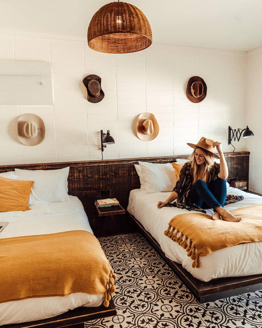 Interior of rooms at Cuyama Buckhorn with hats on the wall and girl sitting on bed