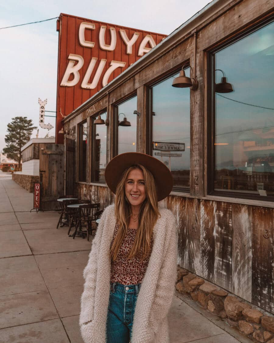 Exterior of the Cuyama Buckhorn with retro signage and girl standing in front with hat