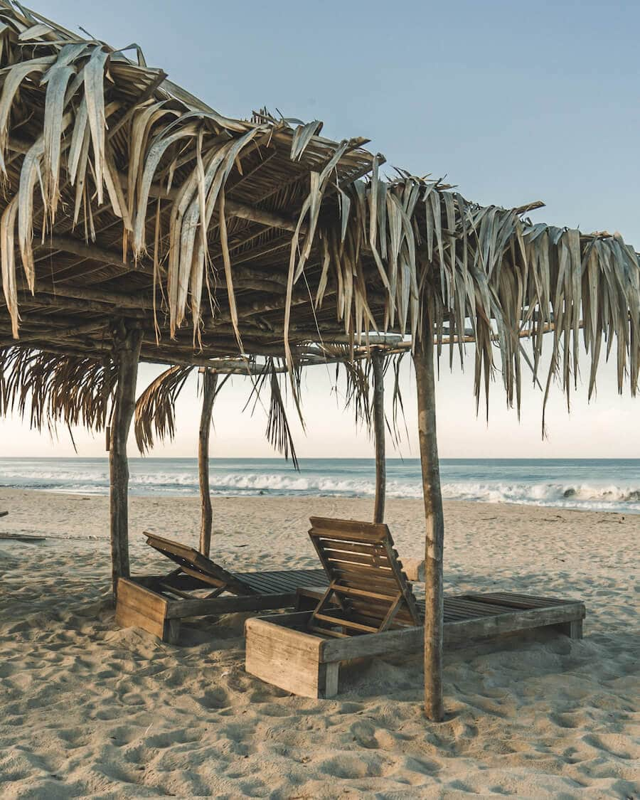 Two wooden lounge chairs on the sand overlooking the ocean