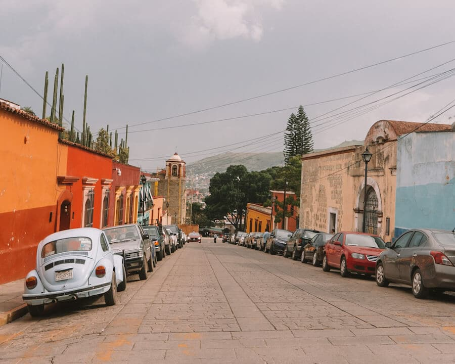 A colorful street in Oaxaca City with an old VW bug