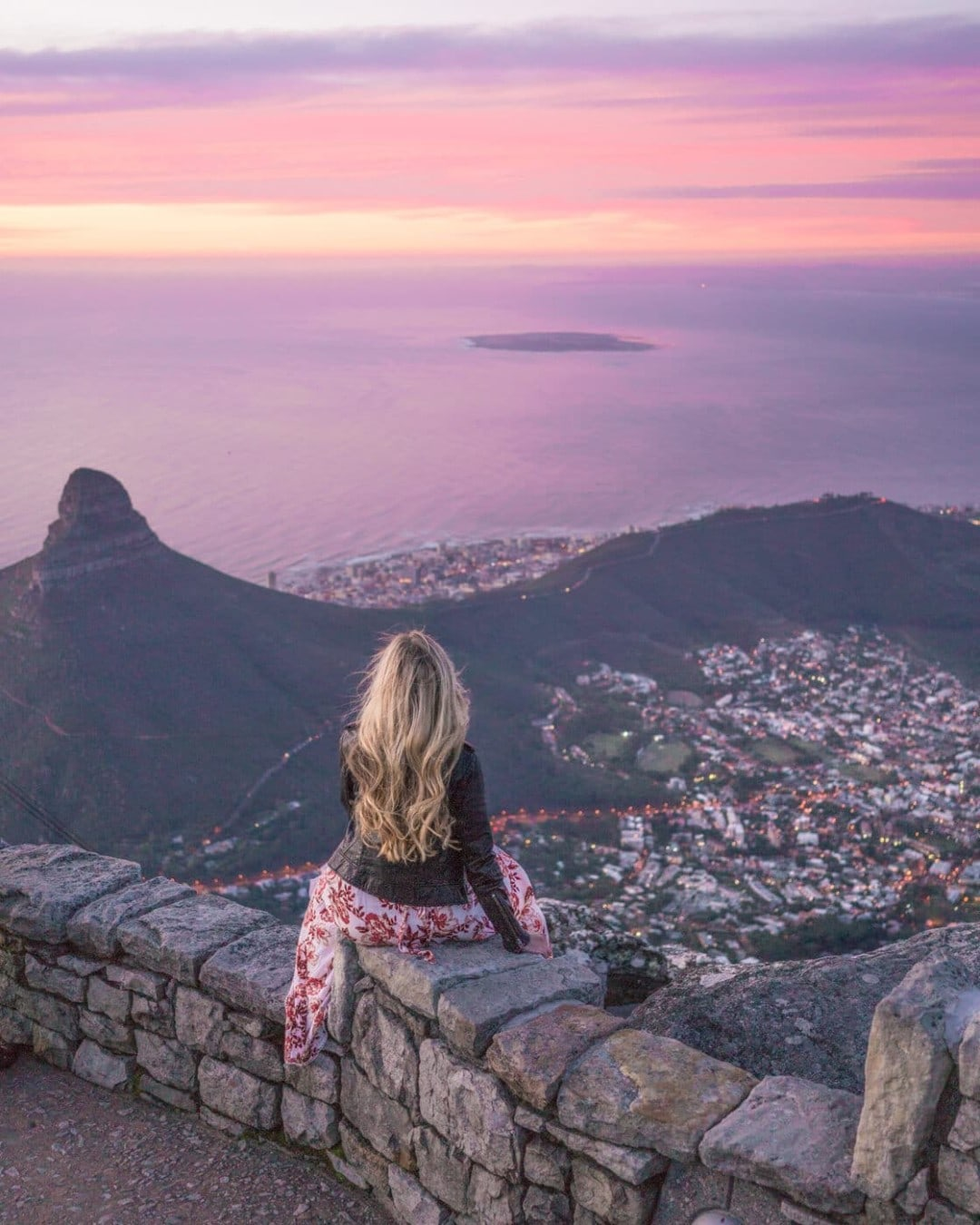 Girl sitting at the top of table mountain at sunset overlooking Cape Town, South Africa