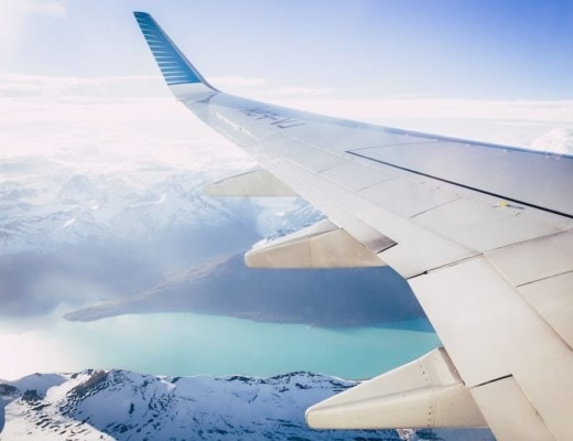 White airplane wing overlooking snowy mountain peaks