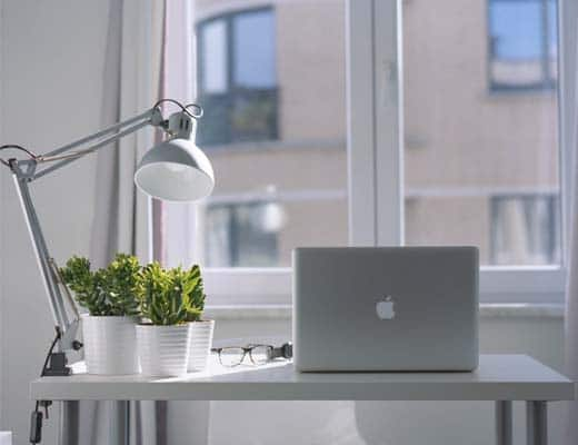 Image of desk with laptop on it and green plants