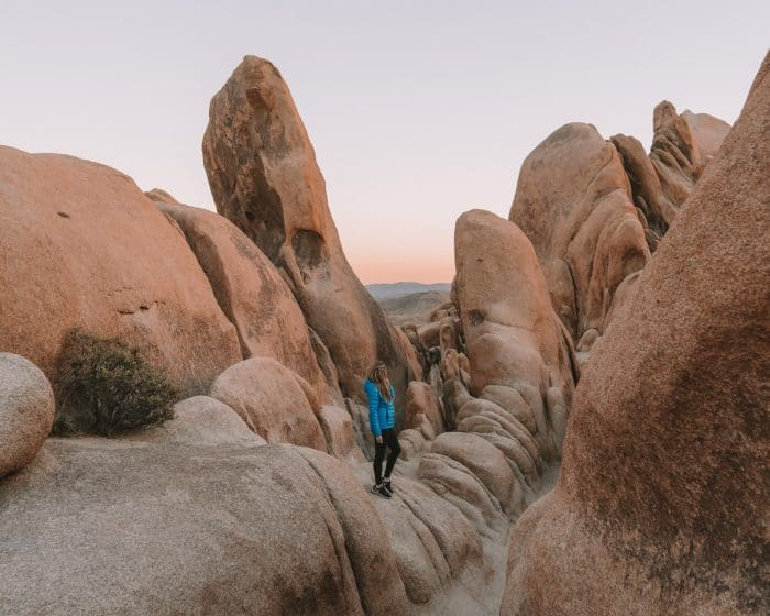 Rock formations in Joshua Tree National Park and girl in blue jacket