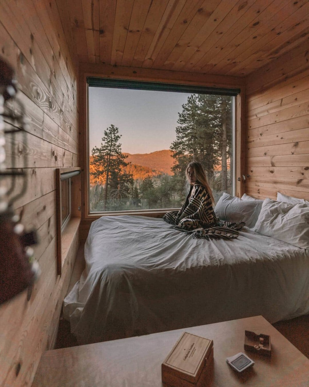 Girl sitting on bed in the Getaway House cabin in Big Bear