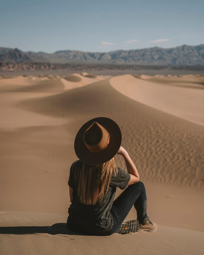 Girl with hat sitting in Mesquite Flat Sand Dunes