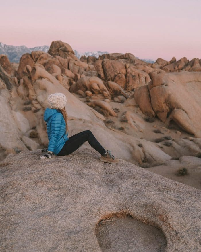 Girl sitting on rock formations in Alabama Hills - exploring is why it's important to get budget travel insurance