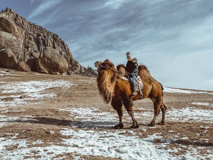 Breanna Wilson riding a camel in Mongolia