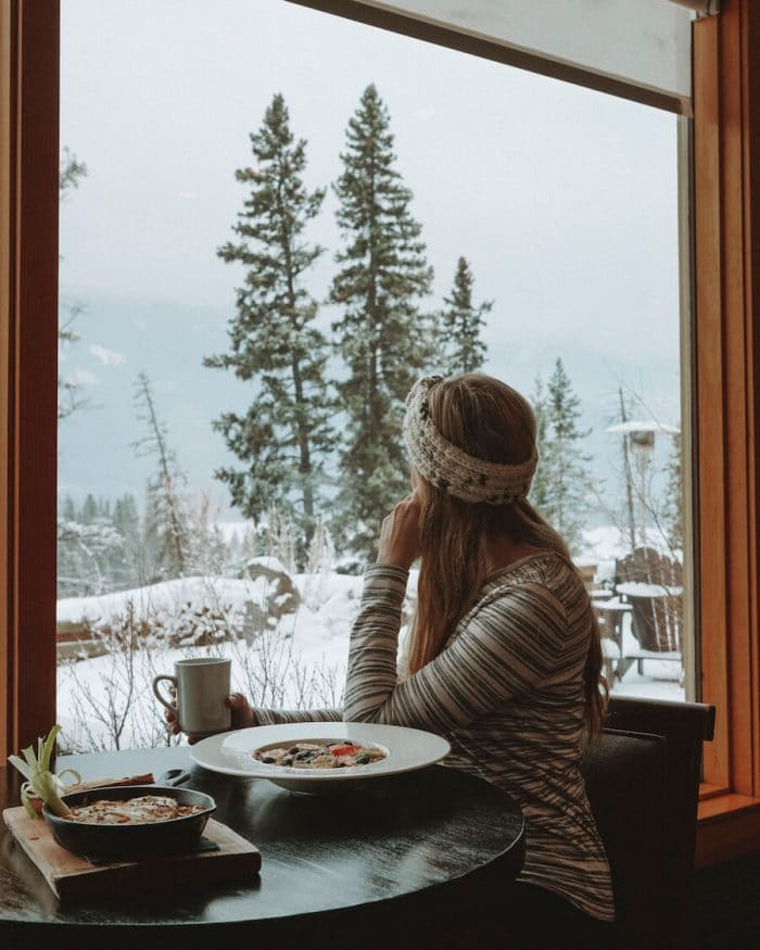 Girl dining at the Juniper Bistro looking out to the snow - where to stay in Banff
