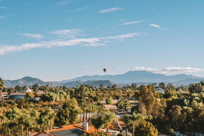 Landscape over Temecula Valley with hot air balloon in distance
