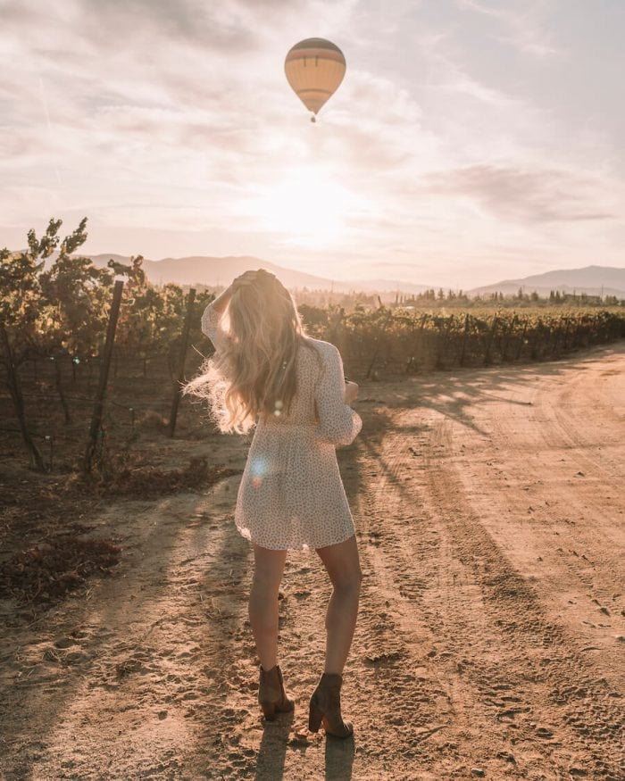 Michelle Halpern walking at Carter Estate Winery with hot air balloon flying overhead