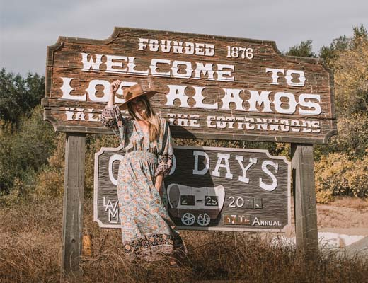 Girl in front of Welcome to Los Alamos sign