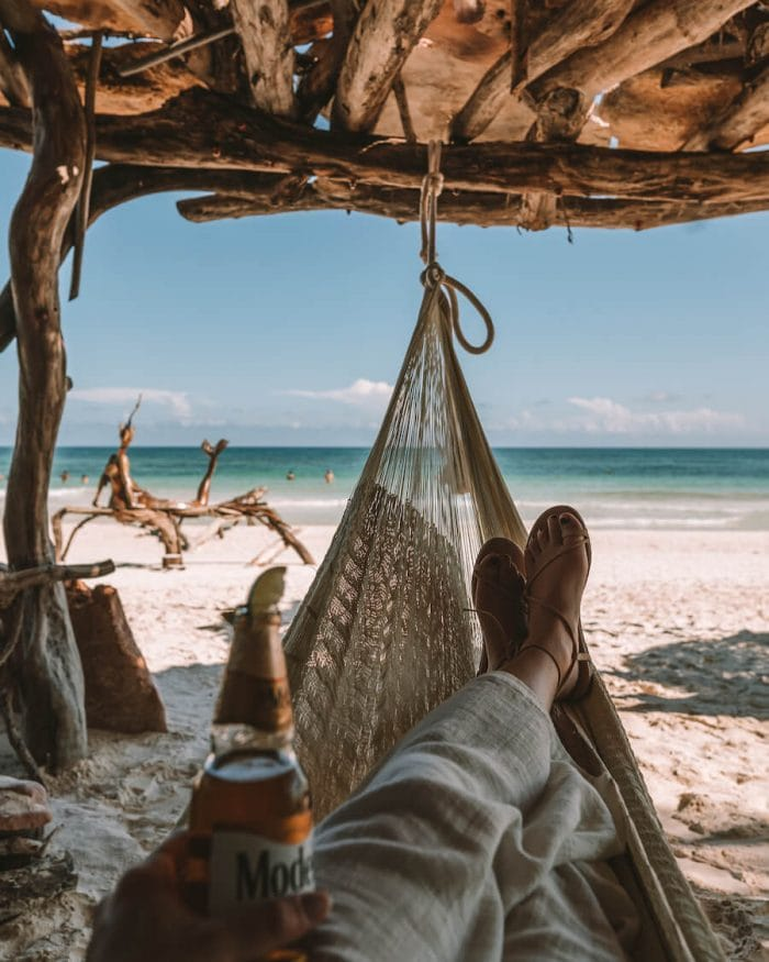 Feet resting in a hammock in front of Tulum beach with Modelo beer