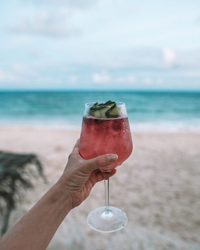 Red colored cocktail by the beach in Tulum