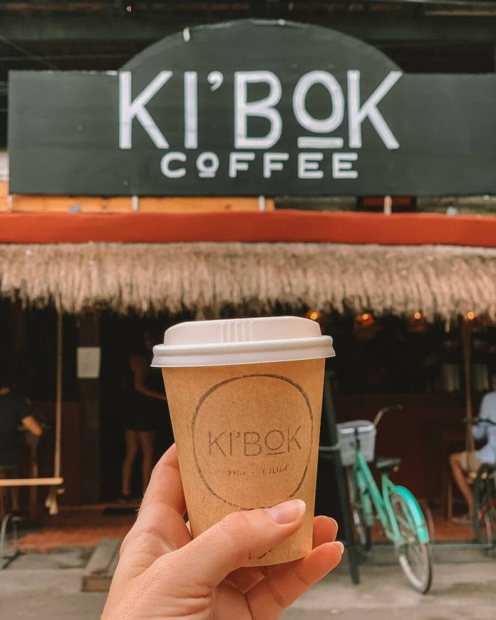 Small late being held up in front of Ki'Bok Coffee, Tulum