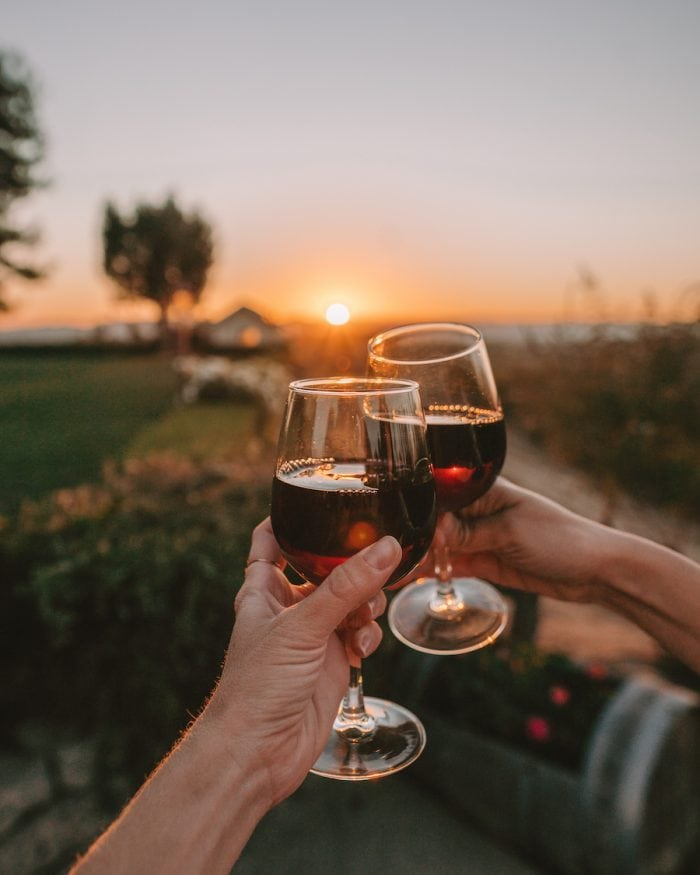 Two glasses of red wine clinking at sunset