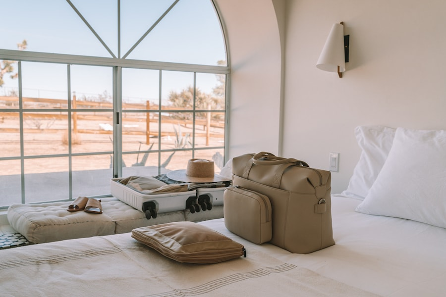 Duffel bag and luggage by Monos sitting out in bedroom