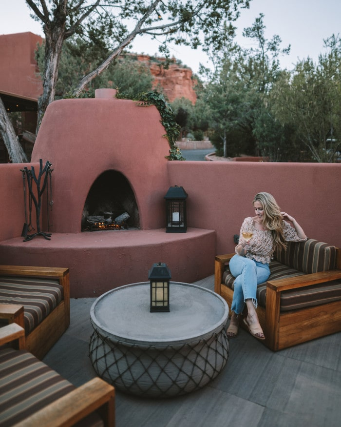 Michelle Halpern by the fireplace with a glass of wine at Enchantment Resort