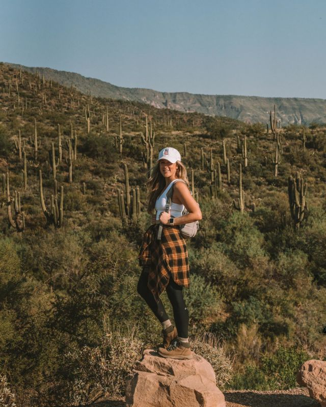 """Camp counselor Michelle reporting for duty 🙋🏼♀️😆 (and yes, that's a rose can on my hat). I'm by no means an """"expert hiker,"""" but I do have some favorite staples for those every-day hikes when I'm out exploring—thought I would share some of them here! Would love to hear what brands and items you love for adventuring.@merrell Waterproof Hiking Boots - This is probably the item I wear that I get asked about most. I love love love these hiking boots. Bought them three years ago and they've served me so well on countless adventures. Most hiking boots are pretty ugly IMO but these ones are *actually* cute, super comfy and never had a """"break in"""" period. Will link again in stories today! Apple Watch - This has been one of the best new additions to my hiking gear because of the distance tracking. There were so many times in Sedona when the watch saved us from missing a turn off or going too far past a certain point of interest because we could track how far we'd walked. @aloyoga - For practical workout pants and tops that you actually feel cute in, Alo is my personal favorite. @dagnedover Dakota Backpack - I love their mini version of this backpack (pictured here) on days when I don't need to be carrying a lot of gear. super lightweight, cute, water resistant, and made of neoprene which is hand washable 👏🏻@rei Flash 18 Backpack - If I need more space in my bag for a day hike I'll use this bag which basically weighs nothing and takes up little to no room in a suitcase. It has a hip belt + sternum strap to take weight off my back and is even hydration compatible.@wandrd PRVKE Lite - If I need my full camera bag on a hike, I'll bring the new PRVKE Lite which is the smaller version of their original camera bag. It has enough space to hold my camera body, a couple lenses + accessories, plus it has a roll top where I can stuff extra warm layers. @backcountry - Overall, one of the best sites for buying outdoor gear and clothing for adventures. When in doubt, always check Backcountry"""